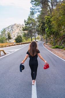 田舎の夏の日にアスファルト道路を歩いている間赤い靴を運び、スタイリッシュな帽子に触れる匿名の裸足の女性の背面図