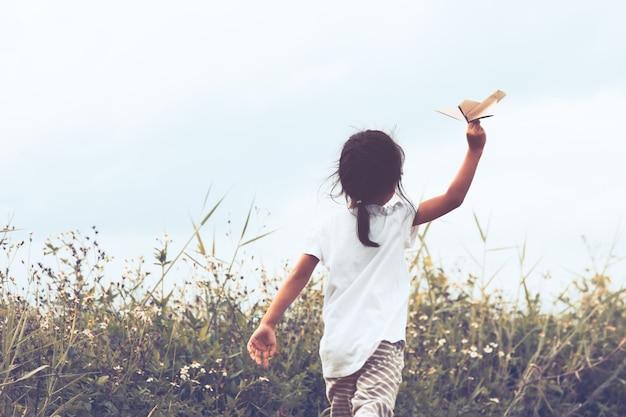 ビンテージ色のトーンで牧草地でおもちゃの紙飛行機を遊んでいるアジアの子供の背面図