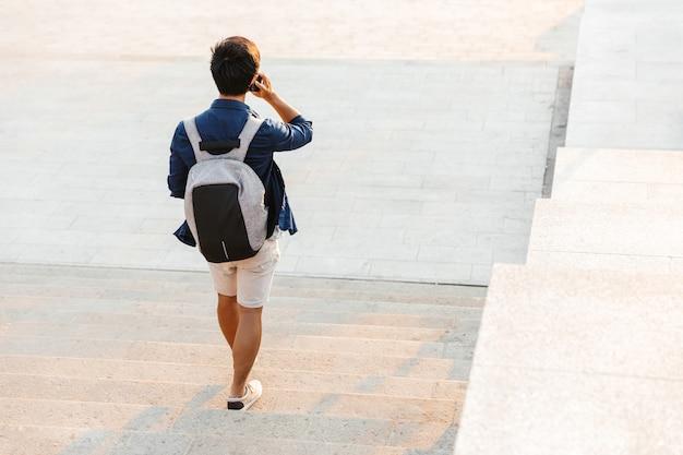 屋外の階段を歩きながらスマートフォンで話しているアジアの男子学生の背面図