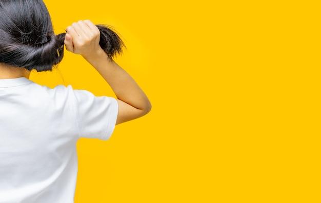 黄色の背景に傷んだ髪を保持しているアジアの女性の背面図。女性の脱毛と薄毛の問題。乾いてもろい黒い長い髪は、スパトリートメントのためにシャンプーとコンディショナーが必要です。