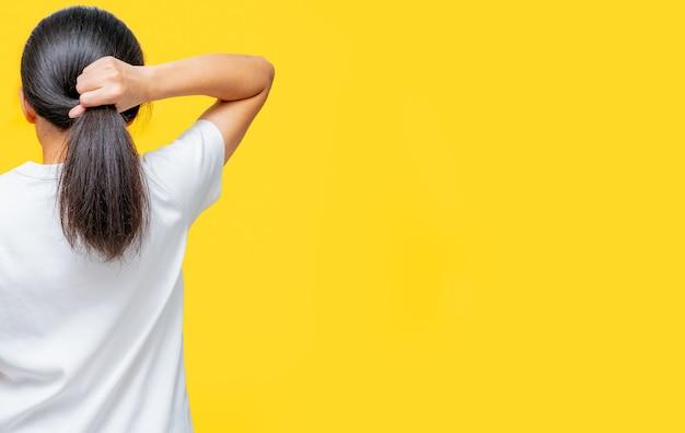 コピースペースと黄色の背景に傷んだ髪を保持しているアジアの女性の背面図。スプリットは女性の髪の問題を終了します。乾いてもろい黒い長い髪は、スパトリートメントのためにシャンプーとコンディショナーが必要です。