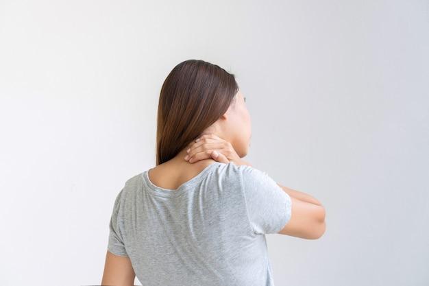 Вид сзади азиатской женщины, страдающей от боли в шее, изолированной на белом фоне. копировать пространство