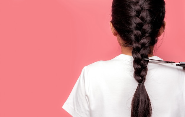 編みこみの髪型を持つアジアの女性の背面図は、がん患者に寄付するためにハサミでカットしています。乳がんの方へのヘアドネーション。ピンクの背景に黒の長いharブレードを持つ女性。