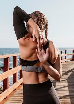 彼女の腕を伸ばしているビーチのそばの屋外の運動選手の背面図