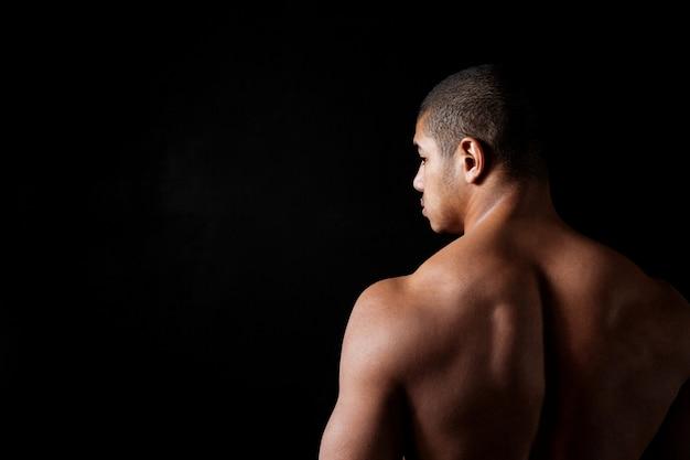 Attracive上半身裸の若いフィットネス男の背面図
