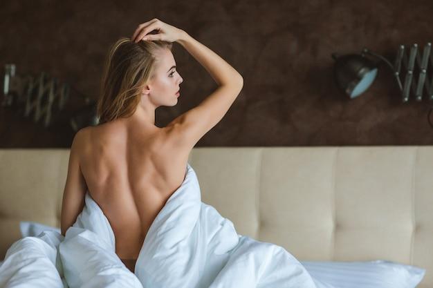 Вид сзади привлекательной соблазнительной женщины, сидящей топлес на кровати