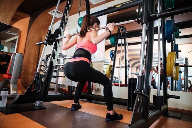 Вид сзади привлекательной молодой спортсменки, делающей приседания со штангой в тренажерном зале