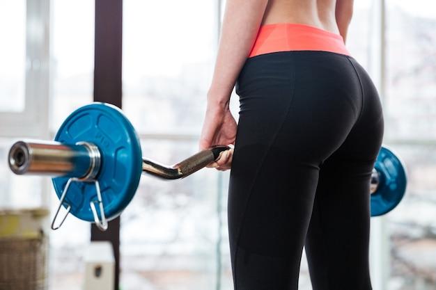 Вид сзади привлекательной молодой спортсменки, тренирующейся со штангой в тренажерном зале