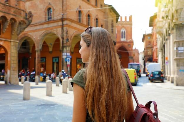 イタリア、ボローニャの古い中世の町を歩いて魅力的な若い女性の背面図。