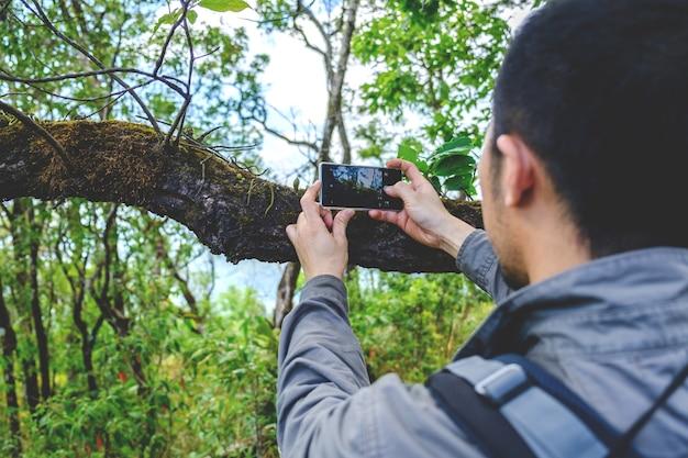 Вид сзади бородатого человека снимает фото с камеры сотового телефона