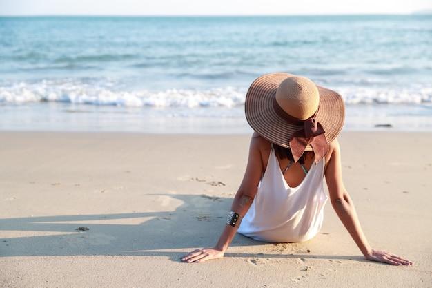 ビーチで帽子を持つ美しいアジアの少女の背面図