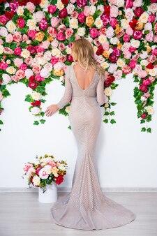 화려한 꽃 배경 위에 포즈를 취하는 긴 드레스를 입은 아름다운 금발 소녀의 뒷모습