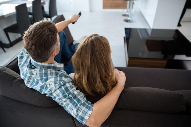 リビング ルームのソファでテレビを見ている美しいカップルの後ろ姿