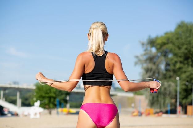 ビーチで縄跳びでストレッチワークをしている美しいほっそりした女性の背面図