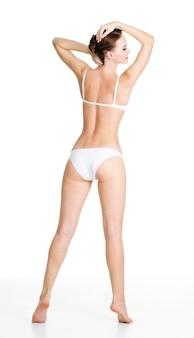 美しいスリムな女性の体の背面図。白で隔離。