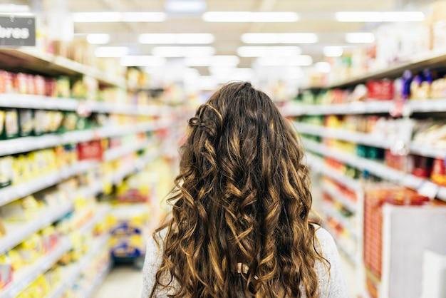 スーパーマーケットで食べ物を買う美しい女性の背面図。市場の食品の概念。
