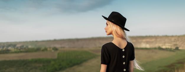 검은 드레스와 모자를 입고 아름 다운 젊은 금발의 여자의 뒷면