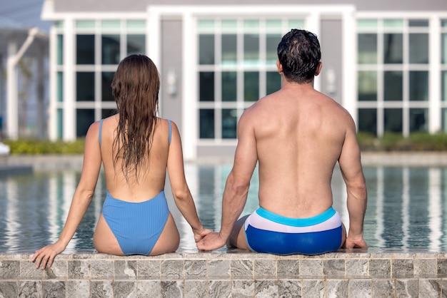 一緒にプールサイドに座っている美しい若いカップルの背面図