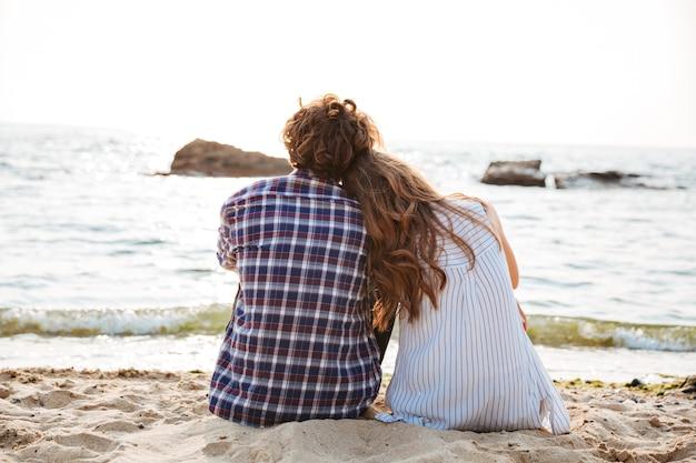 ビーチで一緒に座っている美しい若いカップルの背面図