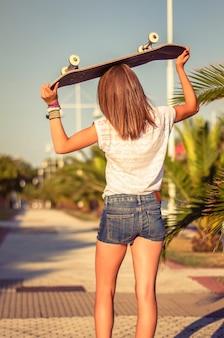 暑い夏の日に屋外でショートパンツとスケートボードを持つ美しい少女の背面図。温かみのあるトーンエディション。