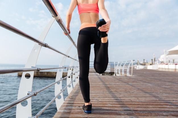 桟橋で脚を伸ばしている美しい若いスポーツウーマンの背面図