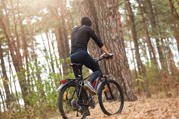 森の道、若い男が森でmtbをサイクリング、時間を費やして黒いトラックスーツを着ているハンサムな男のバイカーの背面図