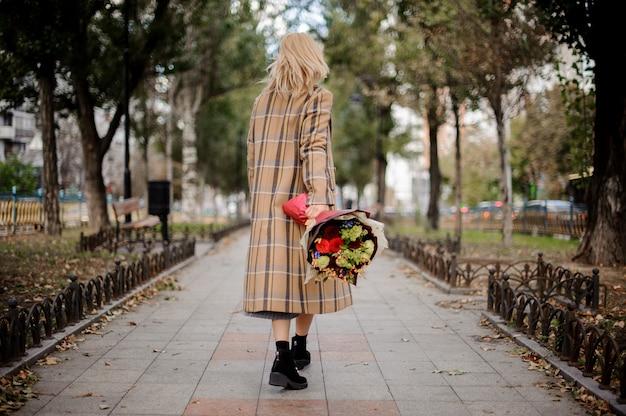 公園の花の花束と歩いている金髪の女性の背面図