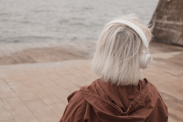 Вид сзади блондинки в наушниках, слушающей музыку или подкаст из приложения для смартфона на фоне моря