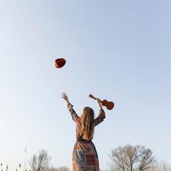 Вид сзади богемная женщина бросает шляпу в воздухе и держит гавайскую гитару