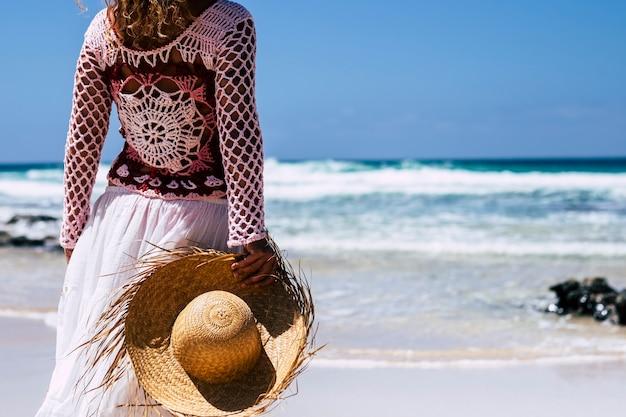 Вид сзади модной женщины в стиле бохо с легкими вьющимися светлыми волосами, наслаждающимися пляжем в одиночестве, глядя на синие океанские волны в летнем путешествии, отпуске, отпуске, образ жизни, держащем соломенную шляпу