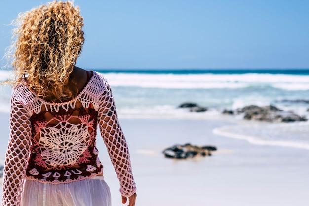 Вид сзади модной женщины в стиле бохо с легкими вьющимися светлыми волосами, наслаждающимися пляжем в одиночестве, глядя на синие океанские волны в летнем путешествии, отпуске, отдыхе, образ жизни
