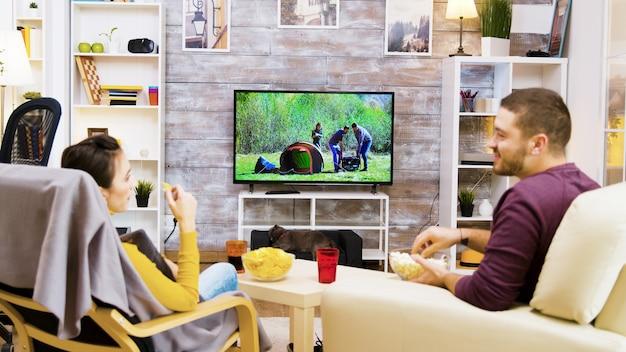 Вид сзади парня и подруги, смотрящих телевизор, сидя на стульях, поедающих чипсы, и кота попкорна, смотрящего на них.