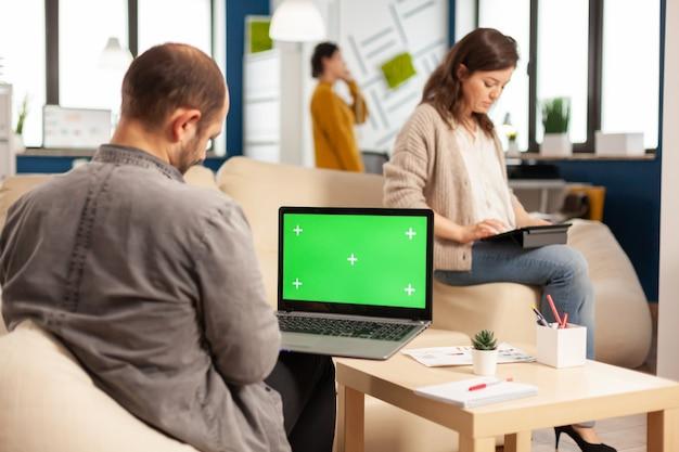 팀이 백그라운드에서 작업하는 동안 녹색 화면이 있는 노트북을 사용하여 소파에 앉아 있는 사업가의 뒷모습