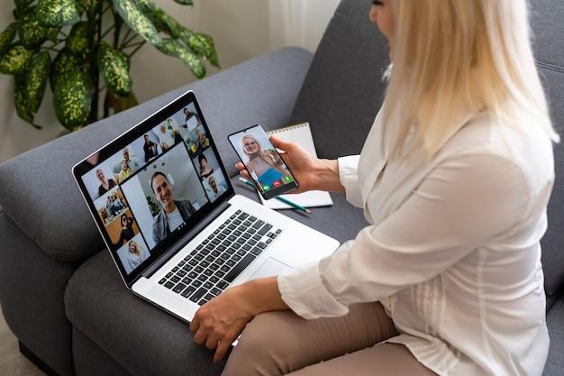 화상 회의 계획에 대해 동료들과 이야기하는 비즈니스 여성의 뒷모습. 화상 통화에서 온라인 회의를 위해 노트북을 사용하는 다민족 비즈니스 팀. 집에서 스마트하게 일하는 사람들의 그룹