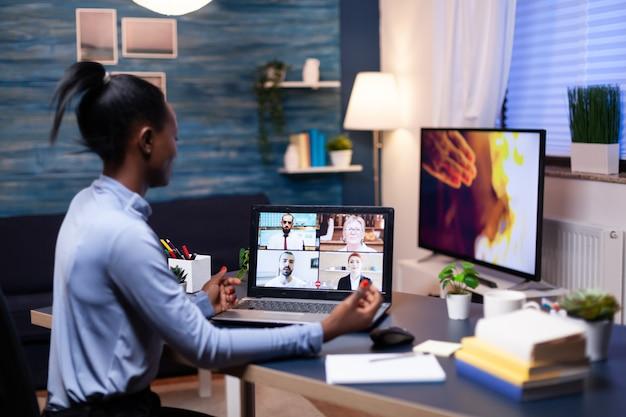 オンラインビデオ通話の過程で同僚と話しているビジネスウーマンの背面図。残業をしている仮想会議で話す最新のテクノロジーネットワークワイヤレスを使用します。