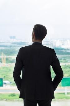 Вид сзади бизнесмен смотрит на город в окне