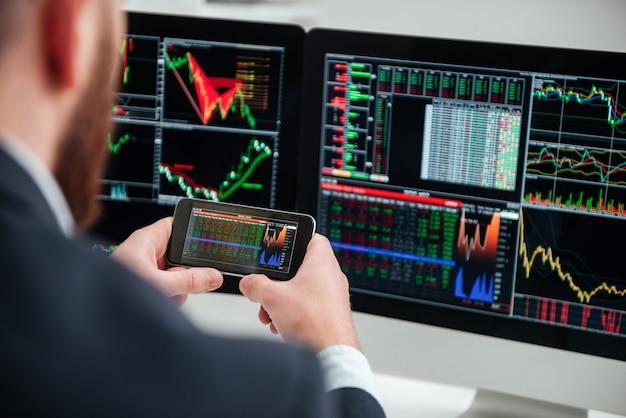 座って、オフィスでコンピューターとスマートフォンで作業しているビジネスマンの背面図