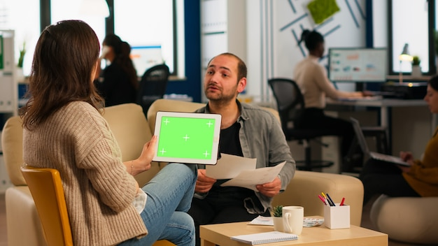 팀이 백그라운드에서 작업하는 동안 녹색 화면이 있는 태블릿을 사용하여 소파에 앉아 있는 여성 사업가의 뒷모습. 크로마 키 디스플레이에 대한 다민족 동료 계획 프로젝트