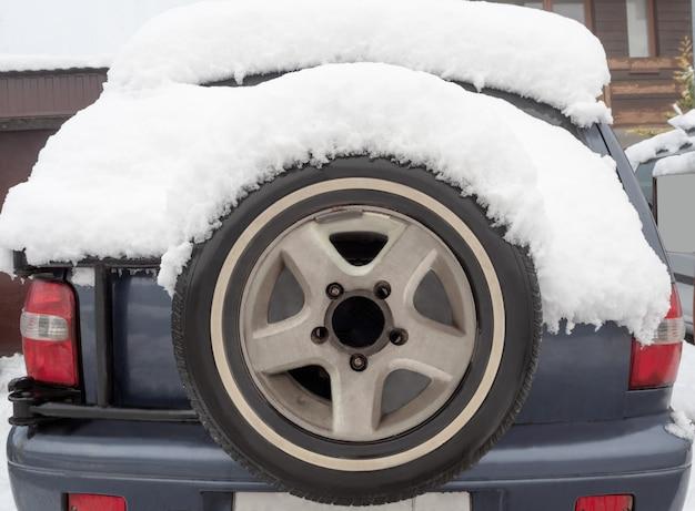 スペアタイヤ付きの車の背面図。雪に覆われたステップニータイヤを搭載したオフロード車