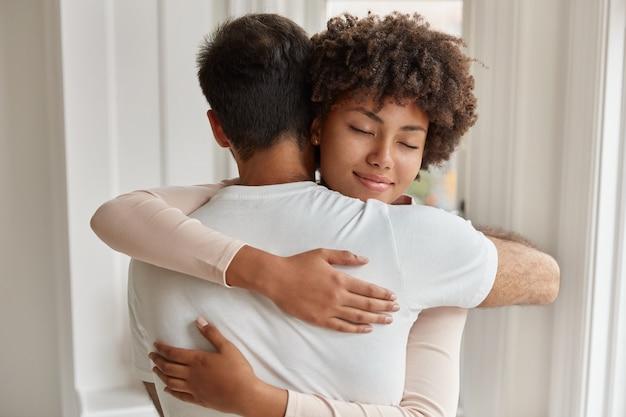 白人男性の背面図は彼女のガールフレンドを抱きしめ、お互いに密接に立ち、愛とサポート、慰め、共感を表現し、良好な関係を持っています。人、ケア、人間関係の概念