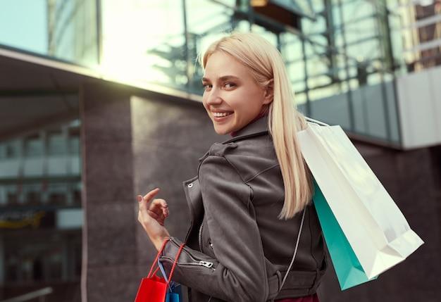 ショッピング中に街の通りに立って、肩越しに見ている紙袋を持つ陽気な女性の背面図