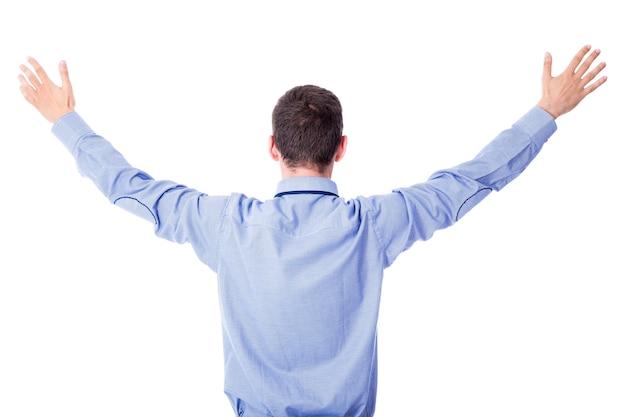 白い背景で隔離の手を上げて陽気な青年実業家の背面図