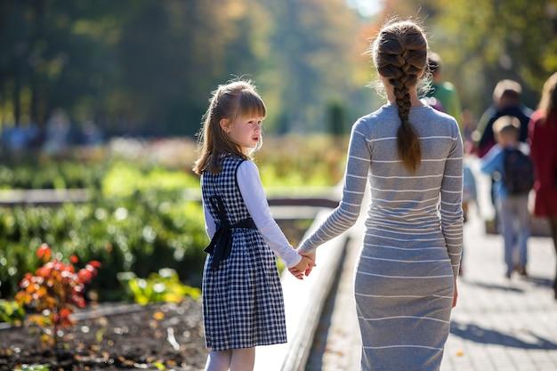 日当たりの良い背景に屋外の暖かい日に手を繋いでいるドレスの子供女の子と母親の背面図。