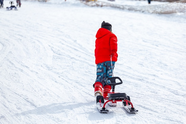 Вид сзади ребенка в санях и бега по снежному склону, проводя время на горнолыжном курорте