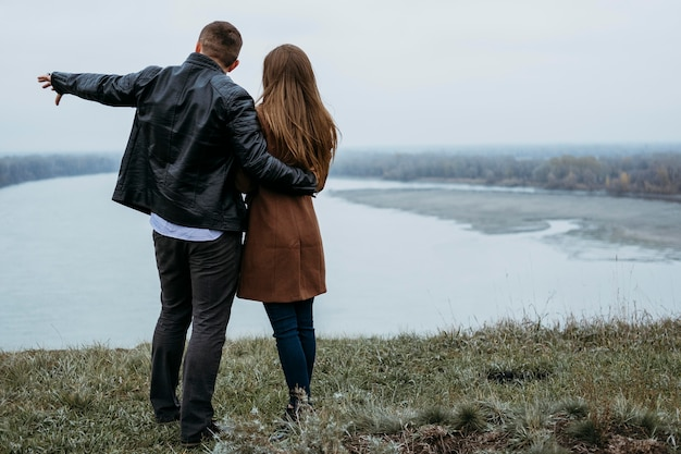 コピースペースで湖の景色を眺めるカップルの背面図