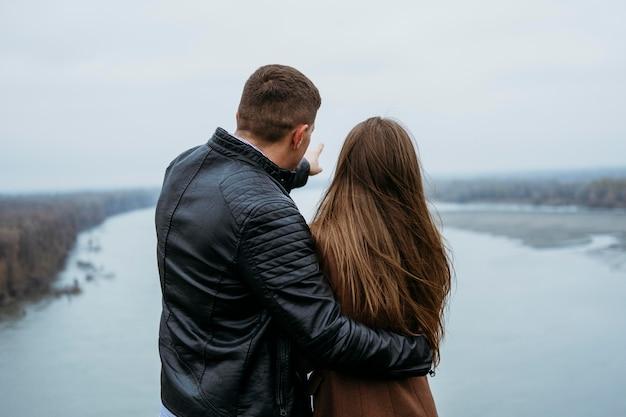 湖の景色を眺めるカップルの背面図