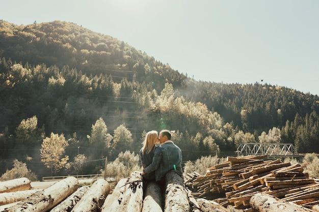 森の薪を抱きしめるカップルの背面図。