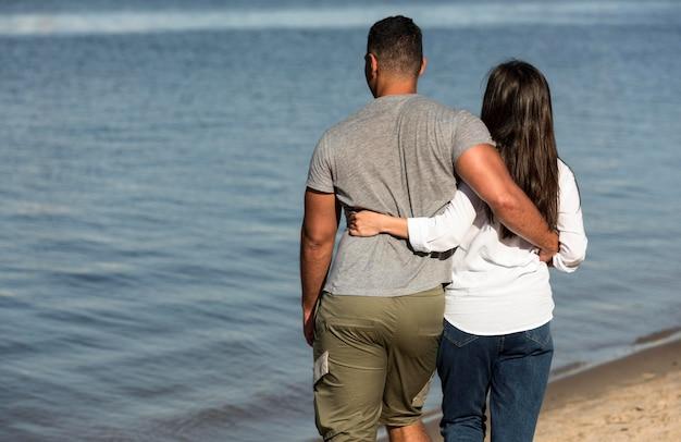 Вид сзади пара, держащая друг друга на пляже