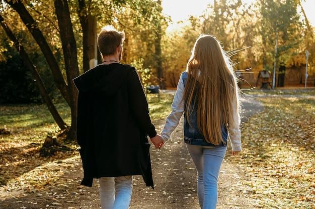 公園で手をつないでいるカップルの背面図