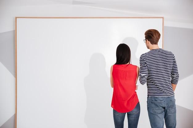 空の空白のボードを見ている展示会のカップルの背面図